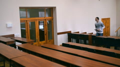 The student leaves the lecture hall. He closes the door behind him. - stock footage