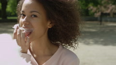 Happy stylish girl holding big cotton candy and eating in sunny park. Stock Footage