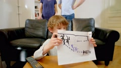 Child Drawing In Table While Happy Parents Watch and Smile Stock Footage