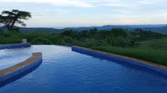 Panorama of swimming pool with tropical mountains and plains in the background  Stock Footage