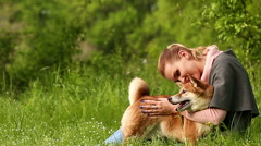 Girl hugging dog Shiba Inu Stock Footage