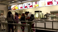 People line up for buying foods inside Ikea store Stock Footage