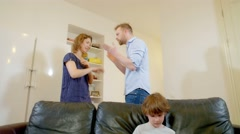 Little boy trying to ignore as parents fight at home. Stock Footage