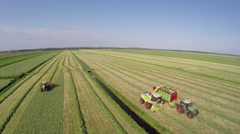 Aerial of tractor raking grass hay and combine harvester harvesting grass 4k Stock Footage