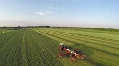 Aerial of tractor raking dried grass almost hay drone following higher 4k Stock Footage