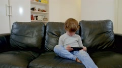 6 years old kid playing computer games at portable game console Stock Footage