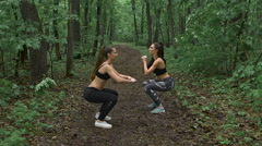 Train in the forest. Two young and beautiful female athletes do warm-up before - stock footage