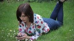 Cute Girl Looking at Smartphone in a Daisy Meadow Stock Footage