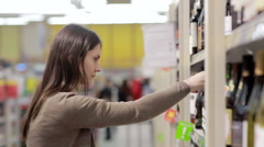Woman selects the wine on the shelves in the store Stock Footage