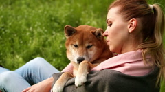Girl gently hugs dog Shiba Inu Stock Footage
