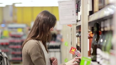 Woman selects the wine on the shelves in the store - stock footage