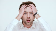 Scared confused man on a white background. Close up - stock footage