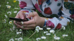 Cute Girl Uses Smartphone in a Daisy Meadow Stock Footage