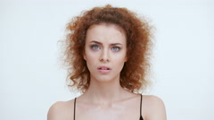 Perplexed confused girl on a white background. Close up - stock footage