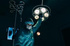 Surgery, medicine and people concept - surgeon in mask adjusting lamp  operating Stock Photos