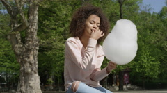 Young afro american woman eating a cotton candy in sunny park. Stock Footage