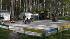 Children ride on electric cars in the park Stock Footage