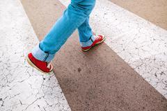 Young teenage person walking over pedestrian zebra crosswalk Kuvituskuvat