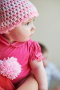 Little baby girl in a knitted hat on hands at mum Stock Photos