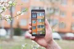 Hand with smartphone taken pictures of multi-storey building Stock Photos