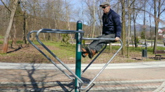 Man is exercising in an outdoor gym Stock Footage