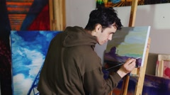 Artist-painter paints a picture in the studio. He is a young and attractive Stock Footage