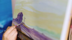 Artist's hand draws a picture. The painting is a typical rural landscape - a Stock Footage