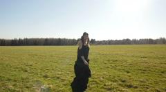 Beautiful girl in long black dress walks on field Stock Footage