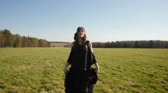 Beautiful girl in long black dress walks on field - stock footage
