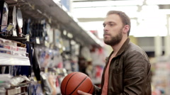 Man chooses sporting goods in store Stock Footage