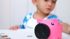 Young boy saving money in pink piggy bank. Stock Footage