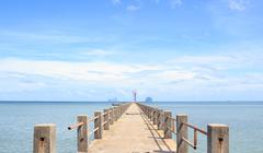 Old wooden and concrete bridge in tranquil sea to find paradise destination w Stock Photos
