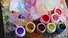 The artist mixes paint. Poppy brush in the paint, and selects the desired shade Stock Footage