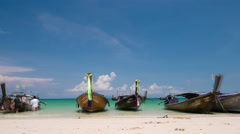 Longtail boats and tourists at beautiful white-sand beach Stock Footage