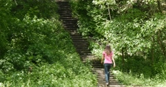 Woman climbing stairs in the woods Stock Footage