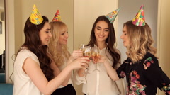 Beautiful girls clink glasses of champagne in the birthday Stock Footage