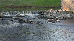 the river blocked by the dam, shoals, rapids on stones - stock footage