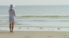 4K Female walking along the shore of the beach alone, in slow motion Stock Footage