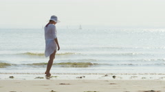 4K Female walking along the shore of the beach, in slow motion Stock Footage