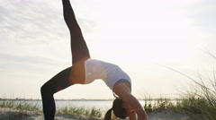 4K Flexible young female in a one legged upward bow yoga pose, in slow motion Stock Footage
