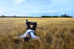 Young asian man relaxing on savanna Stock Photos
