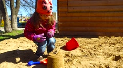 Child girl playing in the sandbox. Girl posing cake out of the sand. - stock footage