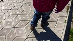 A child walks along the path. The path is covered with diamond-shaped tiles Stock Footage