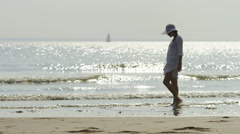 4K Female walking along the beach shore on a nice sunny day, in slow motion Stock Footage