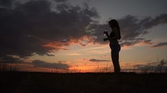 Girl on the sunset drinks water from a bottle Stock Footage