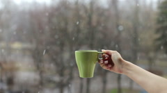 female hand holding a mug of hot drink on a background of falling snow - stock footage