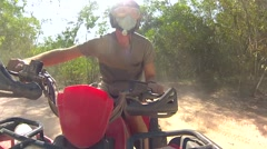 The guy rushes through the Thai jungle and the sand on the ATV quad bike - stock footage