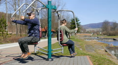 Man and woman exercising in an outdoor gym Stock Footage