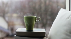 A mug with a hot drink on the books on a background of falling snow Stock Footage