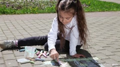 Little girl draws with chalks Stock Footage
